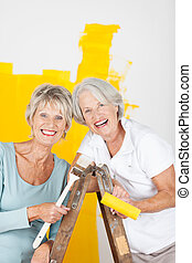 Two happy elderly women painting the house