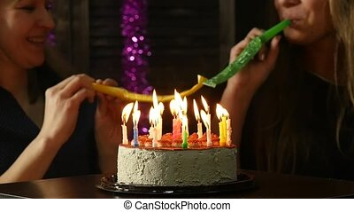 two happy emotional woman blowing out the candles on a birthday cake, candles extinguished. slow motion