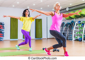 two happy female fitness models dancing zumba doing