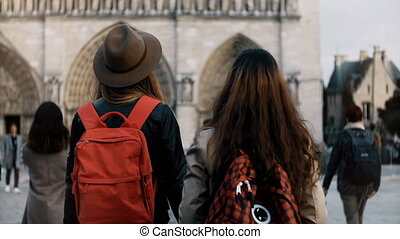 Two happy female walking with red backpacks near the Notre Dame, famous cathedral or church in Paris, France.