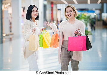 Two happy friends girls with shopping bags walking in mall