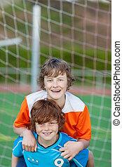 friends having fun on soccer field - two happy friends...