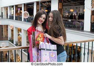 two happy friends shopping in mall