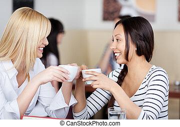 two happy friends talking in a cafe