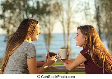 Two happy friends talking outdoors in a balcony