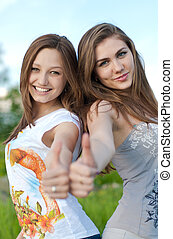 Two happy friends thumbs up