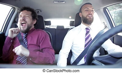 Two happy funny business men dancing in car