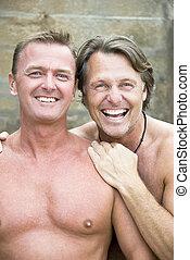 Two happy gay men cuddling.