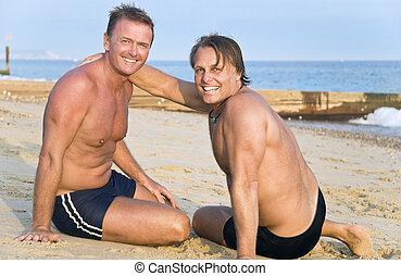 Two happy gay men sitting on beach.