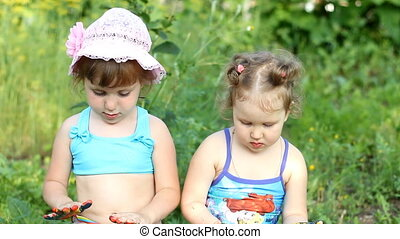 Two happy girl-sisters are sitting in nature in a swimsuit and paint with colors