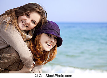 Two happy girls at spring beach.