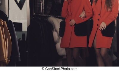 Two happy girls catwalking synchronously in the rich red coats. Slowly