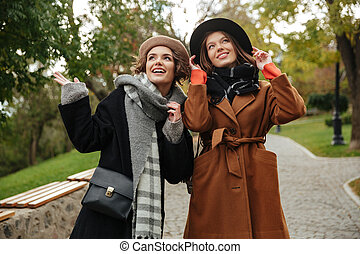 Two happy girls dressed in autumn clothes walking
