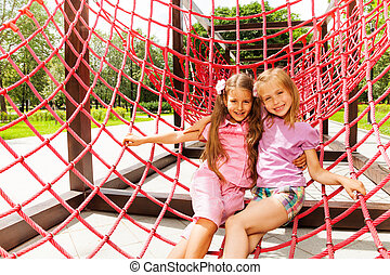 Two happy girls hug on red ropes of playground