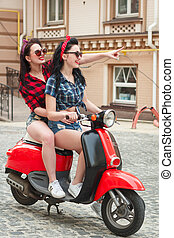 Two happy girls on a moped