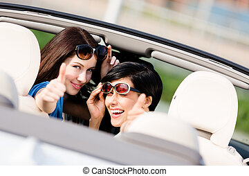 Two happy girls sitting in the car and thumbing up