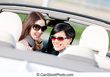 Two happy girls sitting in the car glance back