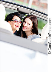 Two happy girls sitting in the car look back