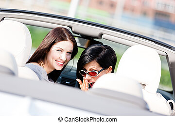Two happy girls sitting in the car turn back
