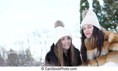 Two happy girls smiling and throwing up snow in the park. Slowly