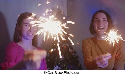 Two happy girls wih sparkler near a Christmas tree