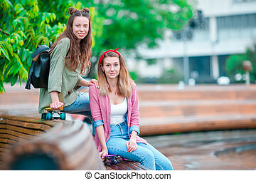 Two happy girls with skateboards outdoors. Active sporty women having fun together in skate park.