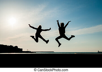 two happy jumping teen girls on blue sky background at sea sunset