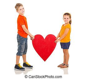 kids holding heart shape - two happy kids holding heart...