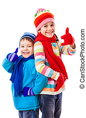 Two happy kids in winter clothes with thumbs up sign