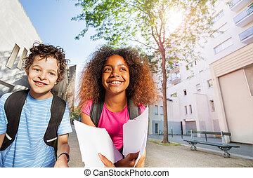 Two happy kids near school smiling
