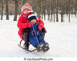Two happy kids in winter clothes on the sled