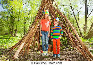 Two happy kids playing Injuns in the forest - Portrait of...