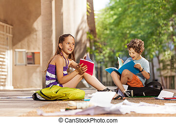 Two happy kids reading books and chatting