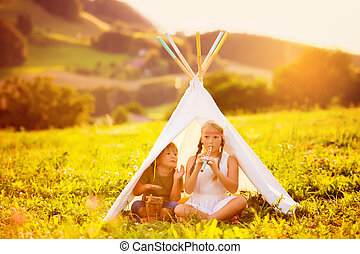 Two happy kids sitting in a tent on a nice warm evening, playing flute and drum music. Brother and sister having good time together