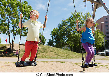 two happy kids swinging on swing at playground