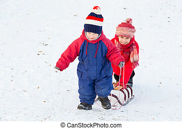 Two happy kids with sled walking on snow slope