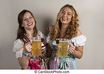 Two Happy Ladies Wearing Dirndls with Beer and Shots