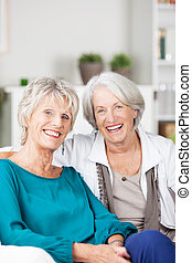 Two happy laughing senior women friends sitting on a sofa in...