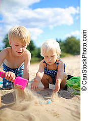 Two Happy little Children Playing in the Sand at the Beach
