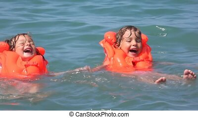 two happy little girls dressed in life jackets swimming in water