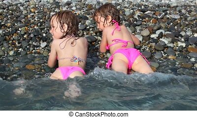 two happy little girls lying on pebble beach with sea surf