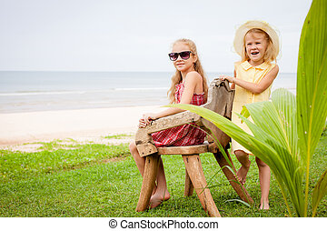 two happy little girls near the beach