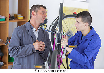 two happy mechanics with tools in a bike repair station