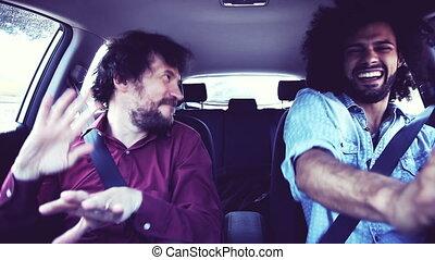 Two happy men dancing in car retro