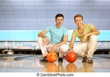 Two happy men sit on floor with orange balls in bowling...