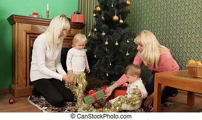 Two Happy Mothers With Babies Playing With Christmas Tree Decorations