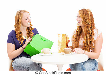 two happy redhead women sitting at a coffee table with shopping bags on white background