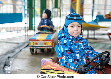 Two happy sibling boys in blue jackets and rain boots playing with big old toy car, outdoors. Kids leisure on cold day in winter, autumn or spring