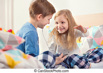 Two happy siblings children having fun and listening music with headphones in bed