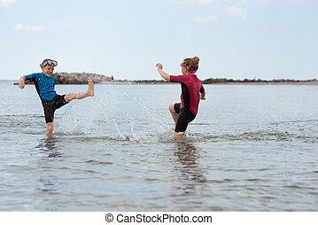 Two happy siblings children in neoprene swimingsuit playin and running in sea